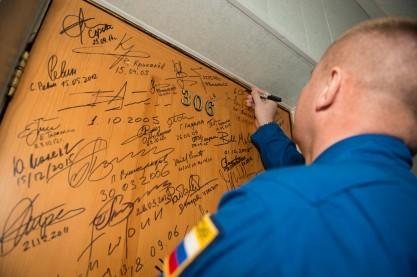 19 de Marzo de 2016: El Comandante de la Soyuz Alexéi Ovchinin de Roscosmos realiza la firma tradicional en su puerta del Hotel del Cosmonauta entre las últimas ceremonias antes de salir con sus compañeros a los últimos preparativos rumbo a su vuelo. Foto: NASA / Aubrey Gemignani.