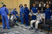 19 de Marzo de 2016: El Ingeniero de vuelo de la Soyuz Jeff Williams saluda mientras aguarda para que la presión de su traje Sokol sea verificado poco antes de su lanzamiento a bordo de la nave espacial Soyuz TMA-20M, Foto: NASA / Aubrey Gemignani.